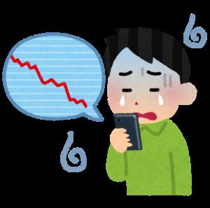 スマートフォンで下落株価チャートを見て嘆く男性のイメージ