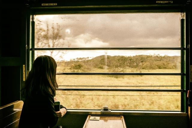 荒野を走る列車の中から車窓を眺める女性イメージ20180307